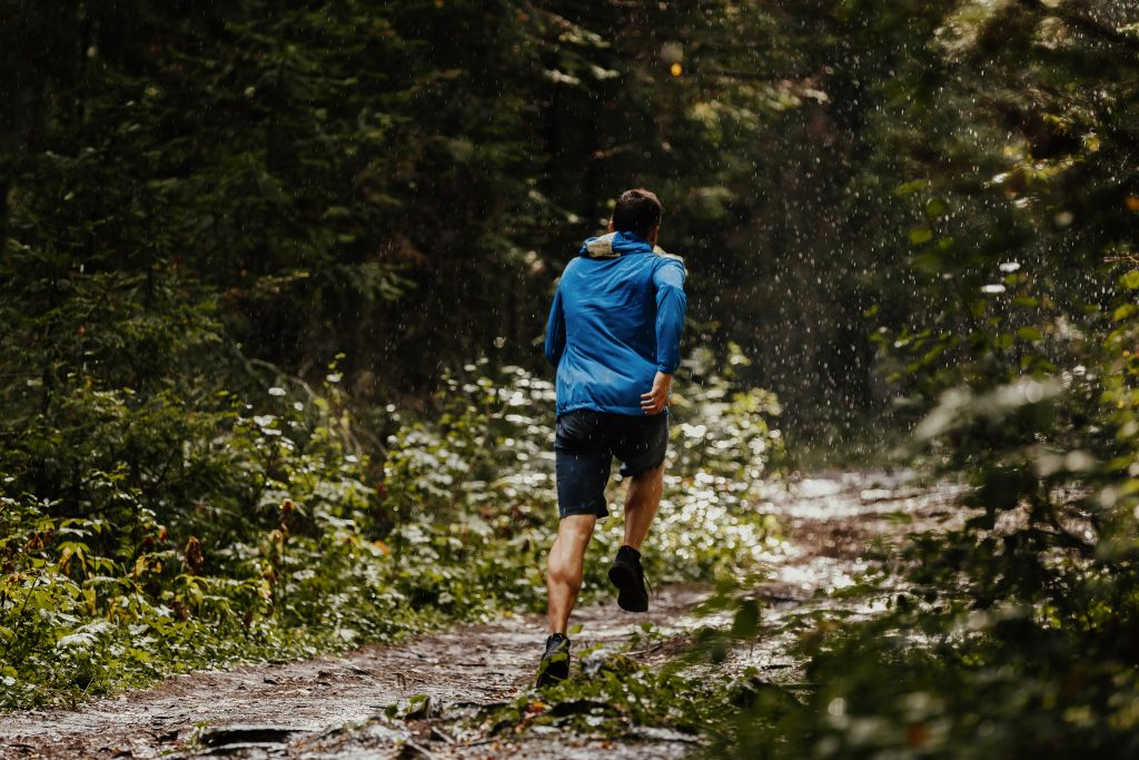 male runner athlete trail running forest in rain